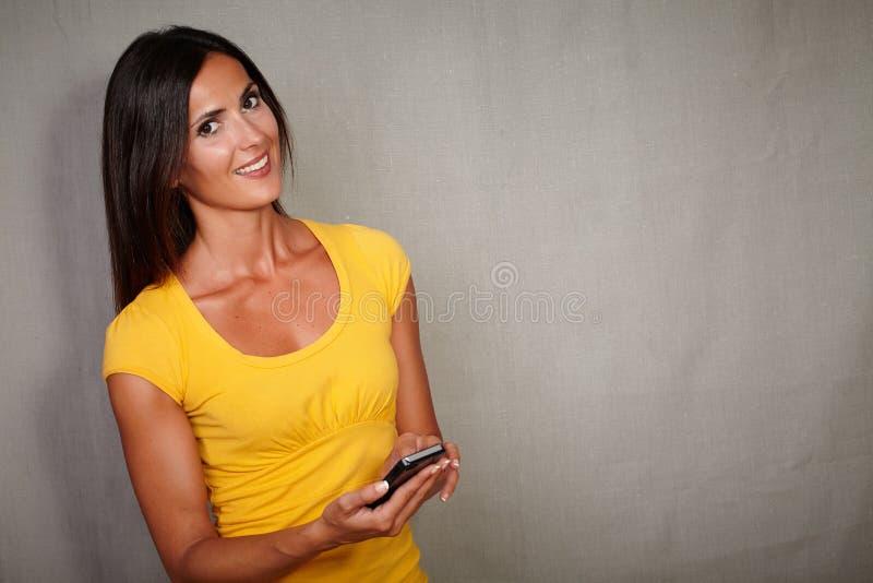微笑确信的妇女,当固定的单元电话时 库存照片