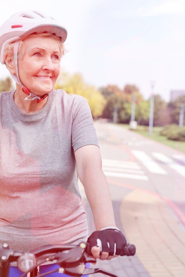 微笑确信的资深的妇女,当骑自行车在公园时 免版税库存照片