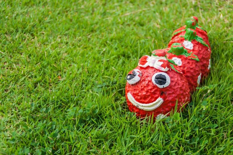 微笑红色蠕虫雕象在庭院里 免版税图库摄影