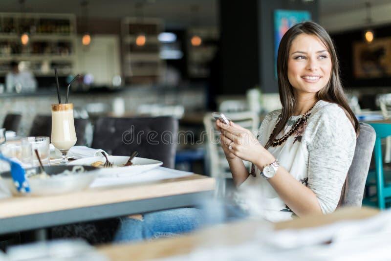 微笑美丽的夫人坐在酒吧和,当举行一个响度单位时 免版税库存图片