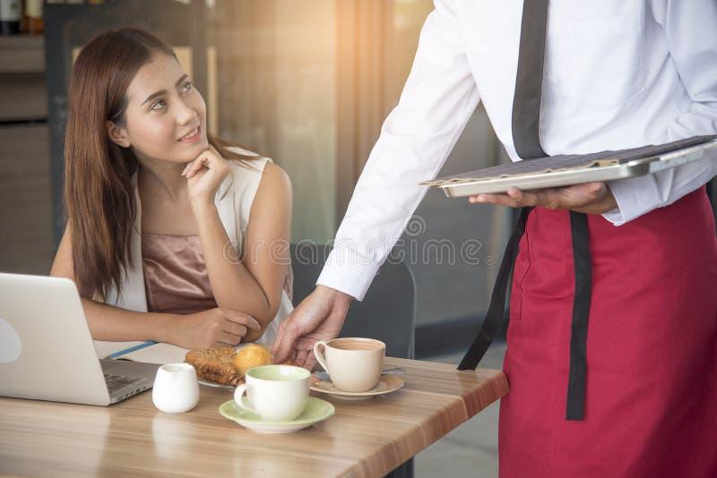 微笑美丽的女商人看英俊的侍者,当供食食物时 免版税库存照片
