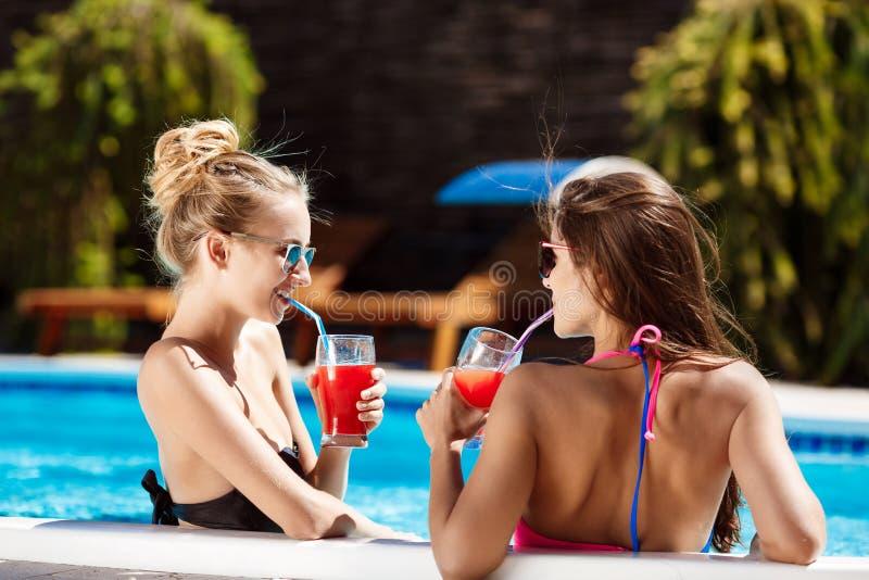 微笑美丽的女孩,讲话,饮用的鸡尾酒,放松在游泳池 免版税库存照片