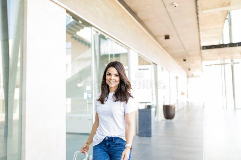 微笑美丽的妇女,当走在商城时 免版税库存图片