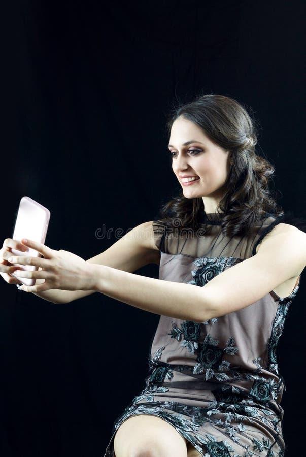 微笑美丽的少妇做自画象 免版税库存照片