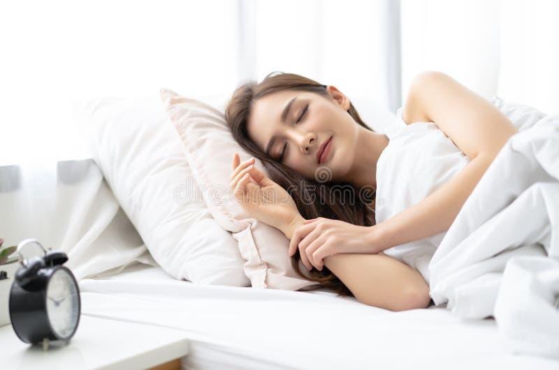 微笑美丽的年轻亚裔的妇女侧视图,当睡觉在她的床上和放松早晨时 享受晚安的夫人 免版税库存图片