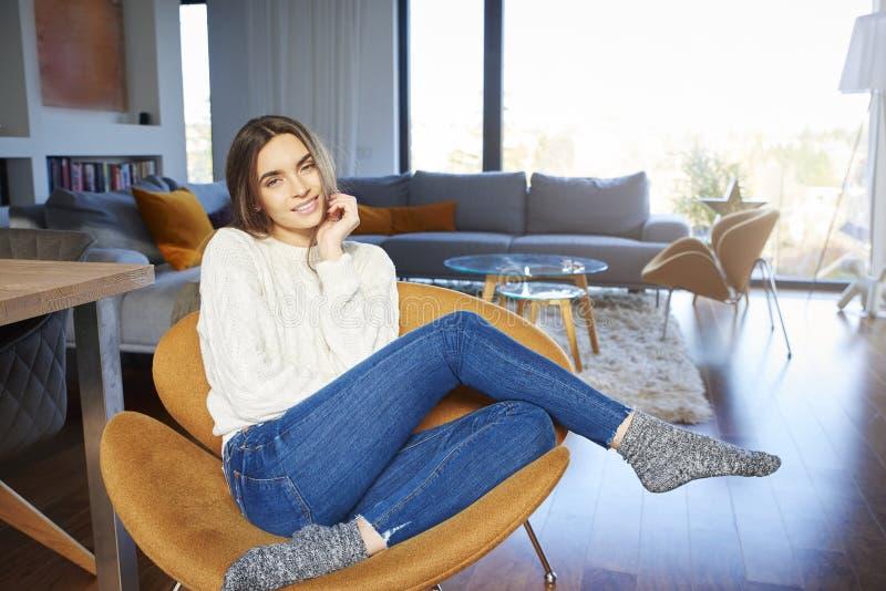 微笑美丽的年轻女人看照相机和,当在家放松在扶手椅子时 图库摄影