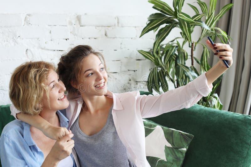 微笑美丽的成熟母亲和她的女儿画象做selfie使用巧妙的电话和,家庭和愉快 免版税库存照片