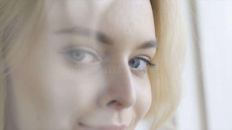 微笑美丽的蓝眼睛的年轻女人特写镜头观看和 r 有迷住的蓝眼睛可爱的白肤金发的夫人 库存照片