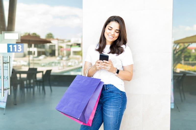 微笑美丽的顾客,当使用智能手机在购物的Cen中时 库存图片