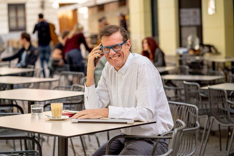 微笑英俊的成熟创造性的自由职业者的商人谈话在手机和,当工作在咖啡馆都市室外时 免版税库存图片