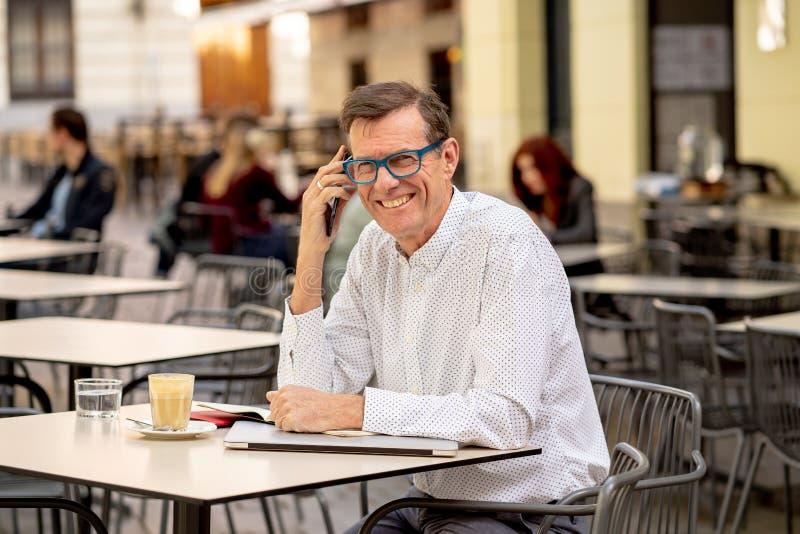 微笑英俊的成熟创造性的自由职业者的商人谈话在手机和,当工作在室外咖啡馆市区时 免版税图库摄影