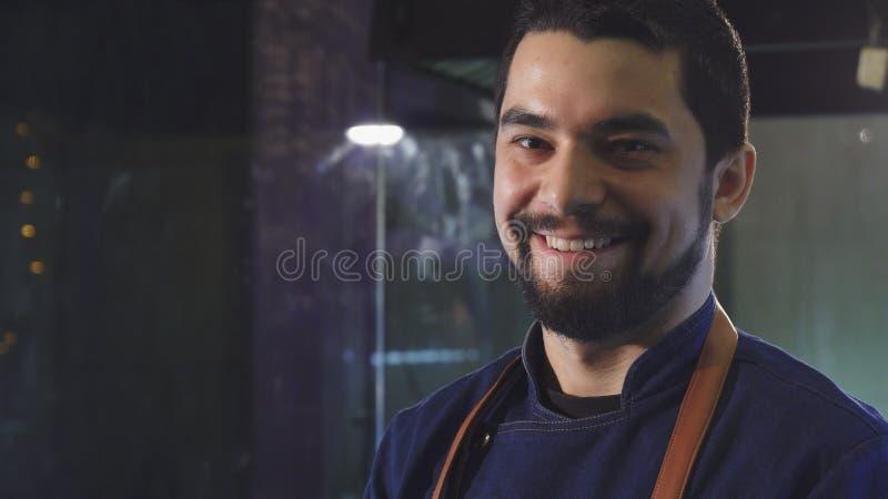 微笑英俊的男性的厨师拿着板材用沙拉 免版税库存图片
