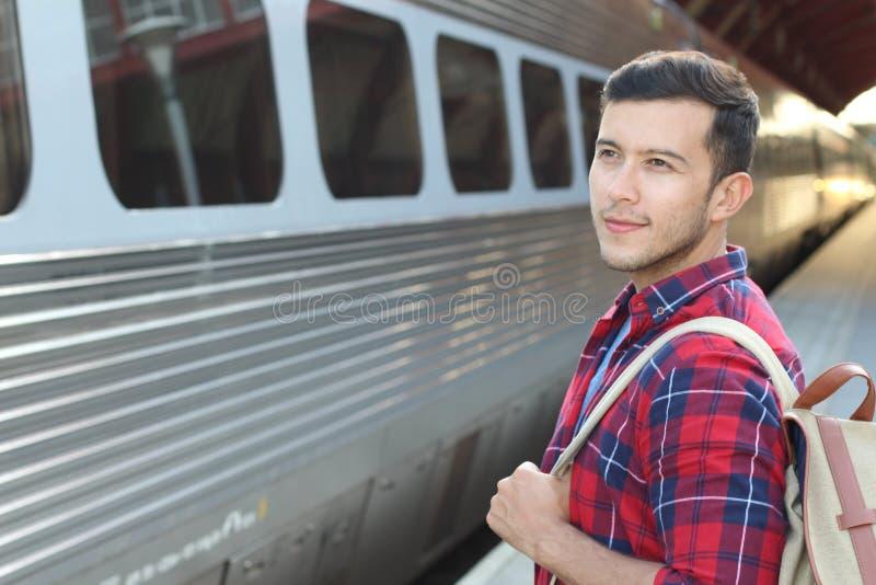 微笑英俊的通勤者,当等待他的火车时 免版税库存图片