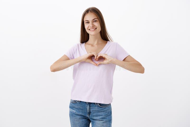 微笑迷人的快乐的年轻白种人的女孩画象偶然T恤杉的快乐表现出显示心脏的爱 免版税图库摄影