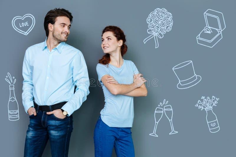 微笑逗人喜爱的夫妇,当庆祝结婚周年时 免版税库存图片