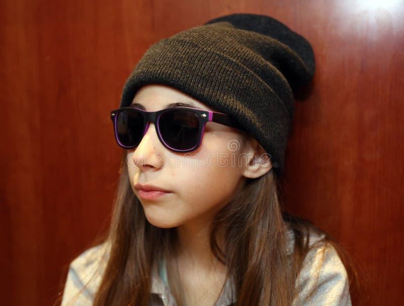 微笑逗人喜爱的女孩戴白色和黑太阳镜 免版税库存照片