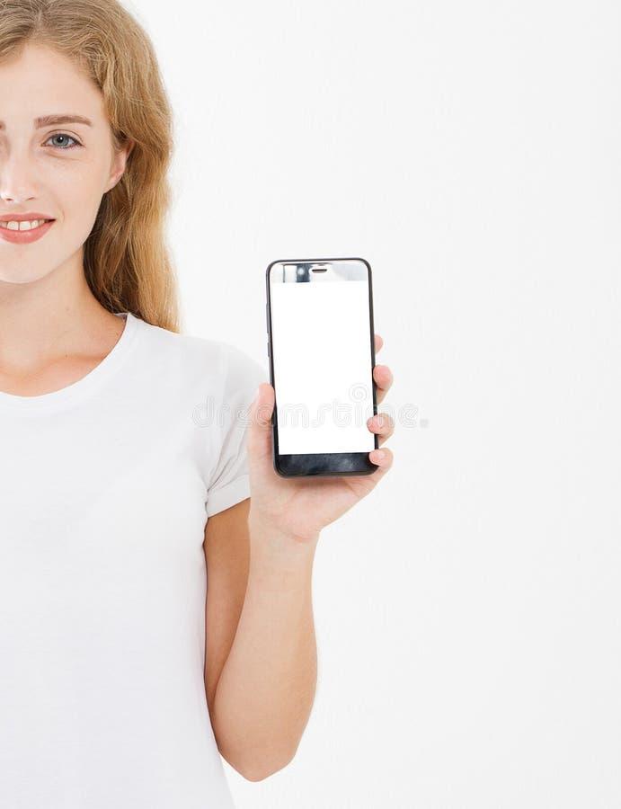 微笑逗人喜爱的女孩,T恤杉举行黑屏在白色背景隔绝的手机的妇女 武器储备智能手机,拷贝空间 库存照片
