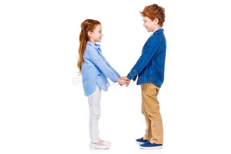 微笑逗人喜爱的愉快的孩子侧视图握手和 库存照片