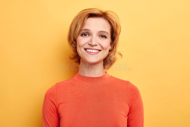 微笑逗人喜爱的正面的女孩看在黄色背景的照相机 免版税库存照片