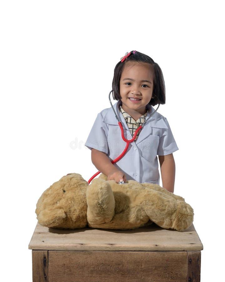 微笑逗人喜爱的矮小的亚裔女孩的医生,当佩带医生的制服使用时 免版税库存图片