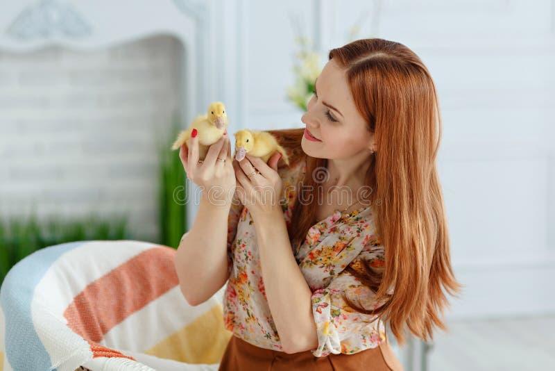 微笑逗人喜爱的红发的女孩拿着鸭子和,复活节 库存照片
