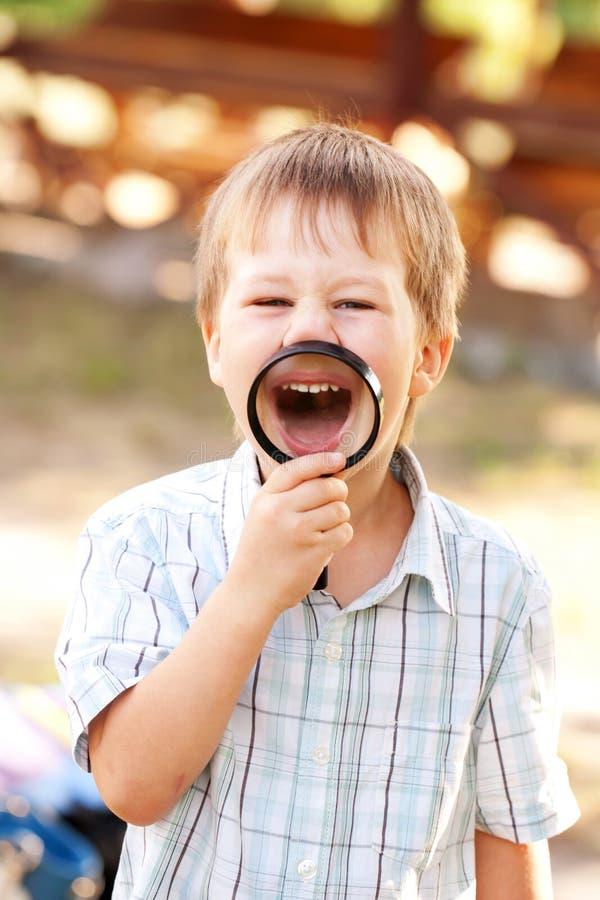 微笑通过放大镜的小男孩 免版税库存图片