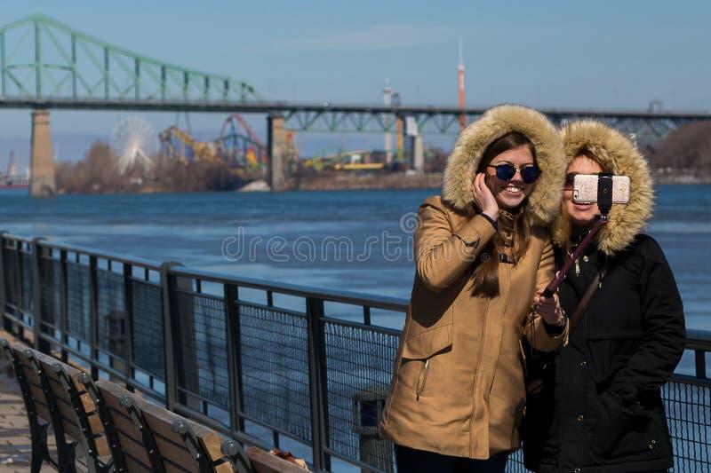 微笑采取在Montreal's旧港口的温暖地加工好的少妇一selfie 库存照片