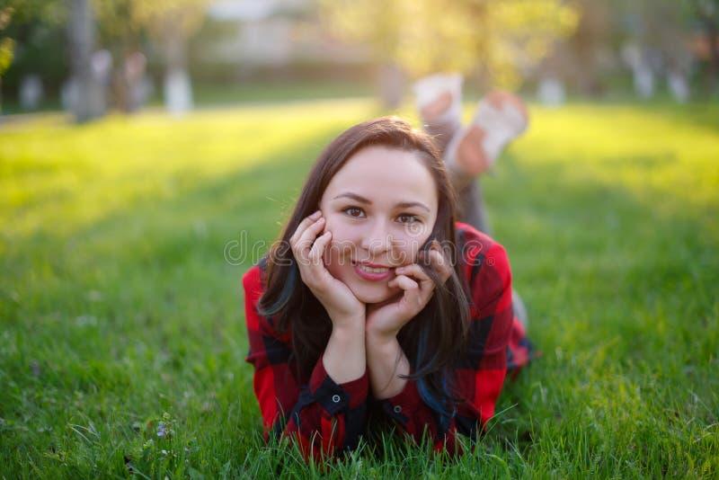 微笑青少年的女孩说谎在草在一好日子和,有微笑在草坪的公园的被开发的身体的女孩 免版税图库摄影