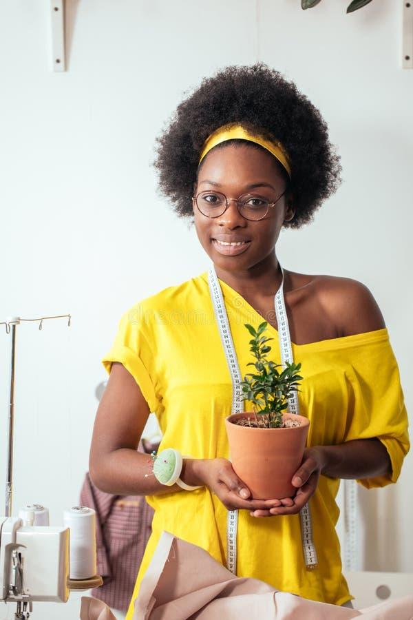 微笑非洲的女孩看照相机在手上的拿着花盆 库存照片