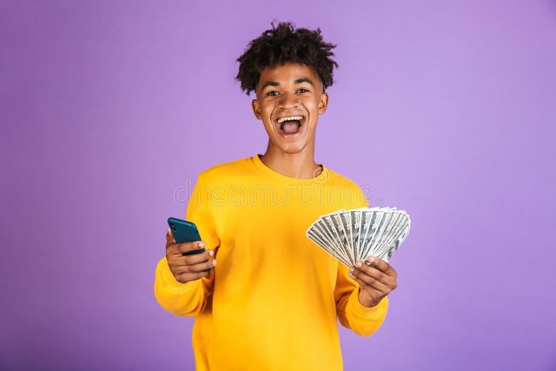微笑非裔美国人的人的画象,当拿着smartphon时 免版税库存图片