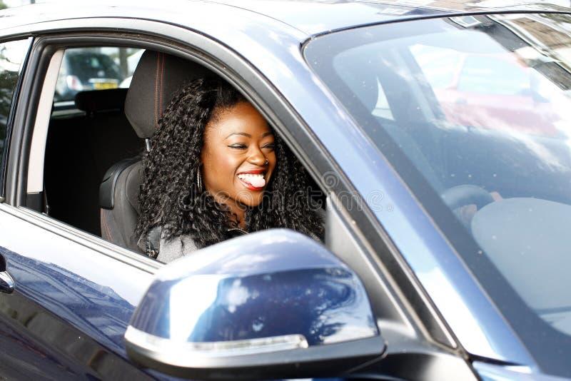 微笑非洲的妇女,她驾驶她的汽车 免版税图库摄影