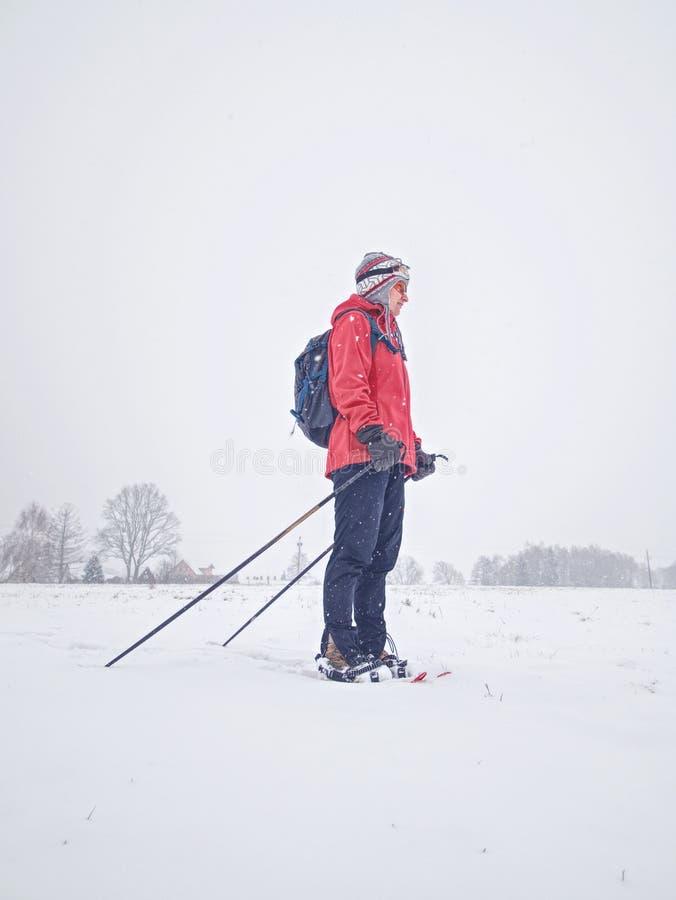 微笑面孔体育在雪靴的女孩步行在多雪的草甸 免版税库存图片