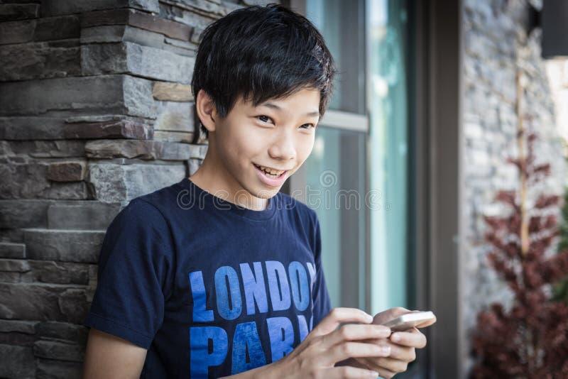 微笑,使用智能手机的亚裔十几岁的男孩 库存照片