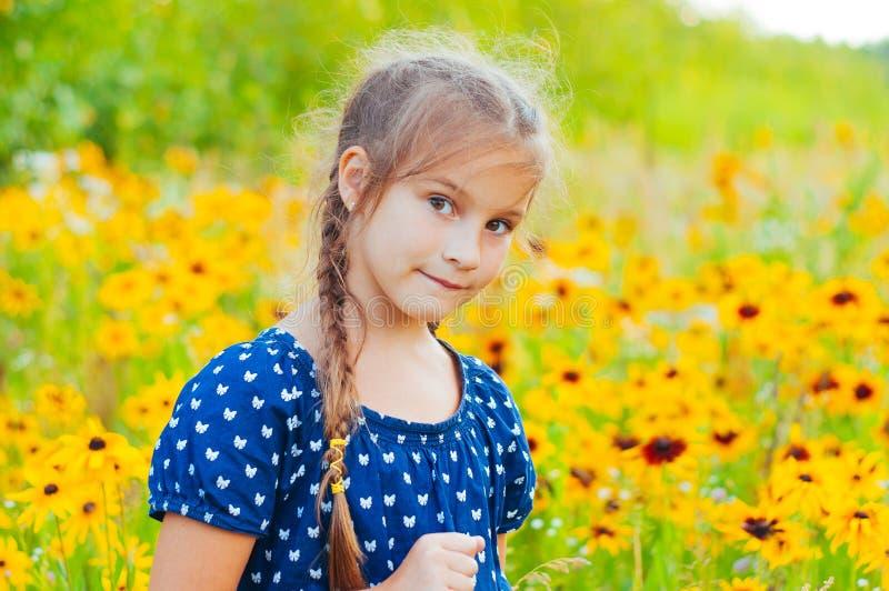 微笑,在与黄色花的领域的一小可爱的女孩的画象 免版税图库摄影