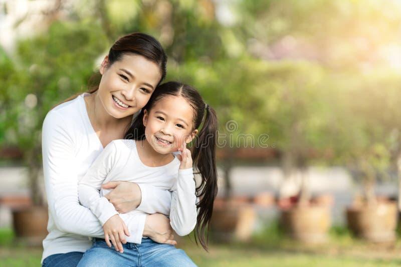 微笑,坐和看照相机的年轻愉快的亚裔母亲和一点逗人喜爱的女儿画象室外公开自然公园 免版税库存照片
