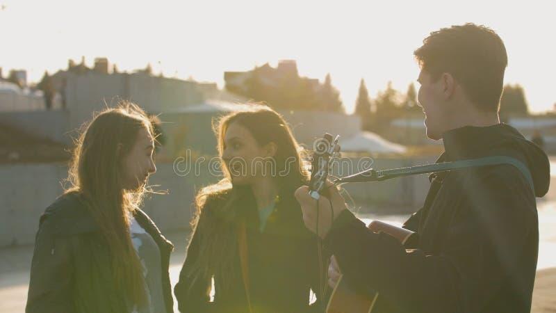 微笑,当人使用在吉他对日落的两个女孩户外时 免版税图库摄影