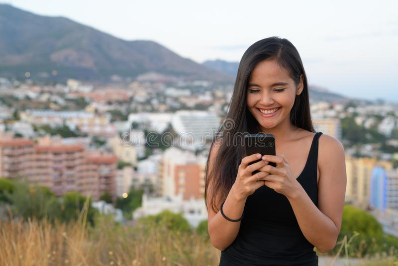 微笑,当使用电话在小山顶部时的年轻美丽的亚裔旅游妇女 免版税图库摄影