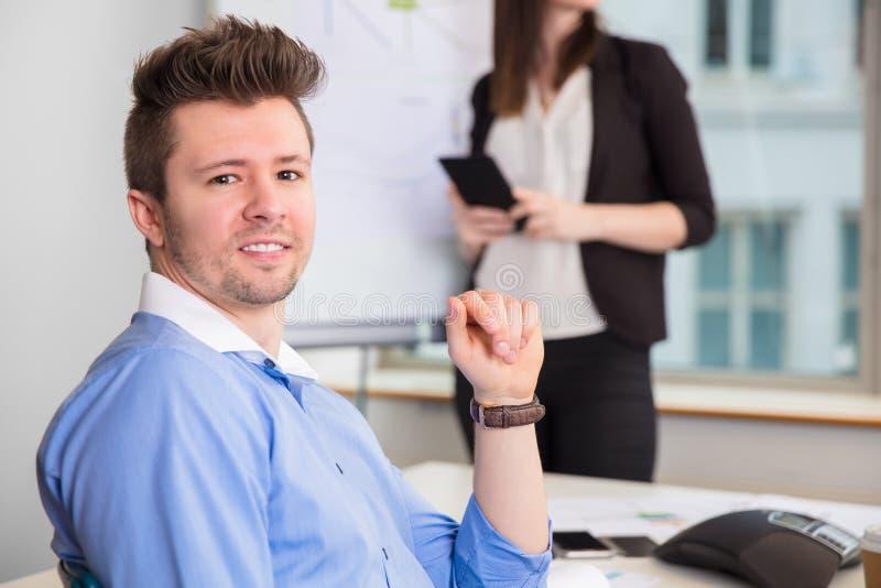 微笑,当同事站立在办公室时的确信的商人 库存照片