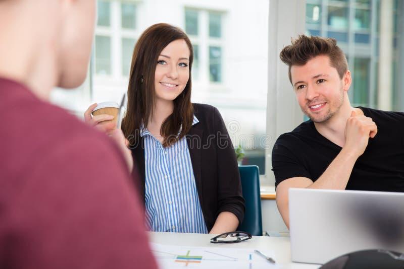 微笑,当看同事对书桌时的商人 免版税库存照片
