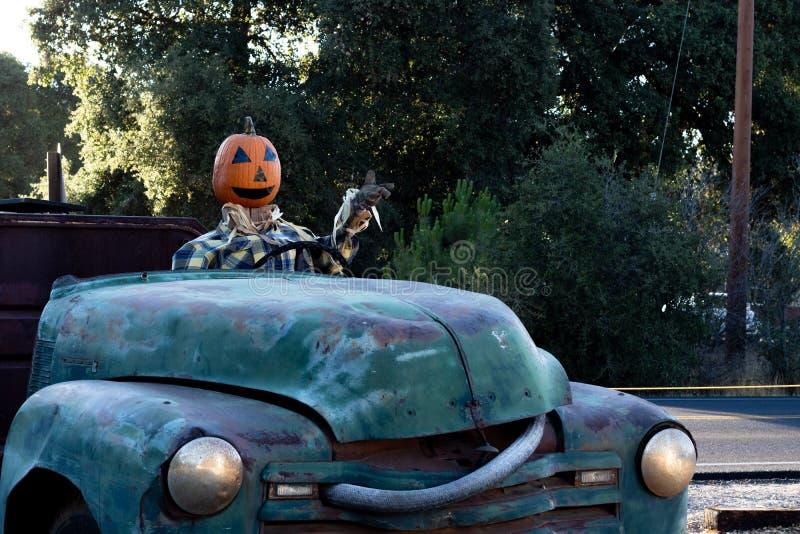 微笑,愉快,欢迎,驾驶一辆老卡车的乐趣友好的南瓜头稻草人到万圣夜收获党 免版税库存图片
