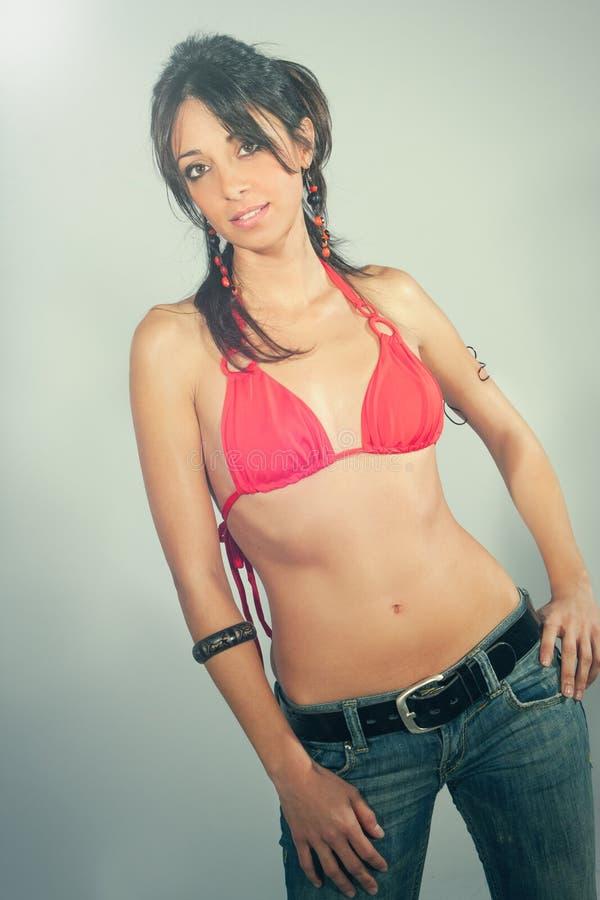 微笑,美丽的年轻深色的妇女 泳装和牛仔裤 免版税库存图片