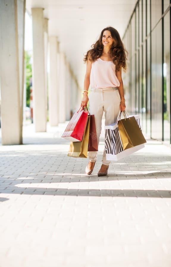 微笑,走与五颜六色的购物袋的棕色毛发的妇女 免版税库存图片