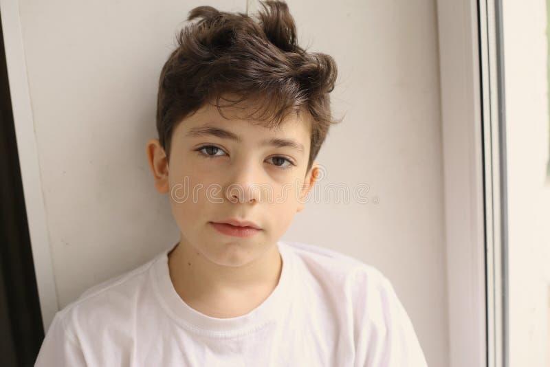 微笑紧密在白色T恤杉的画象的粗野的少年男孩 免版税图库摄影
