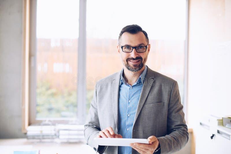 微笑40岁研究手提电脑的英俊的商人在办公室 库存图片