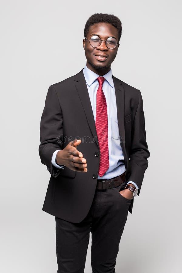 微笑年轻愉快的非洲的商人,当给在灰色时的握手 库存照片