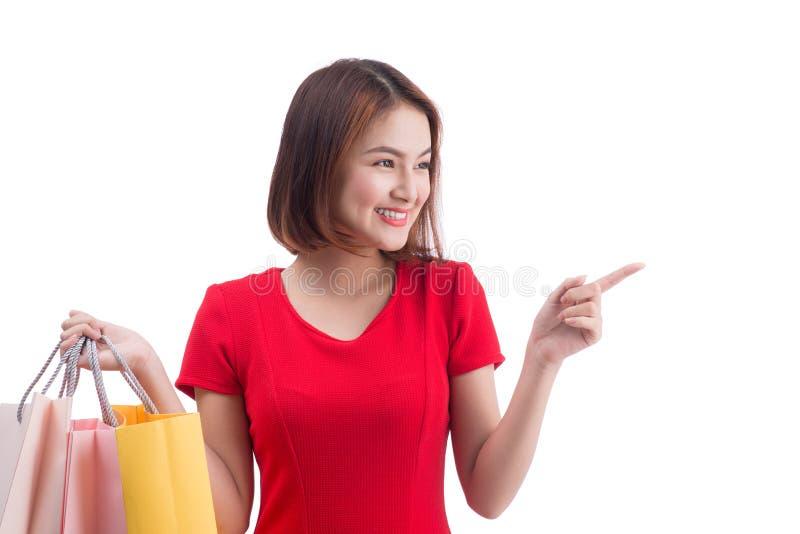 微笑购物的妇女快乐和愉快举行的购物袋指向 在白色隔绝的亚裔女性顾客 图库摄影