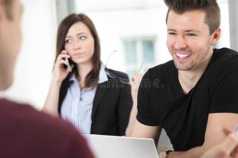 微笑年轻的商人,当看同事时 库存照片
