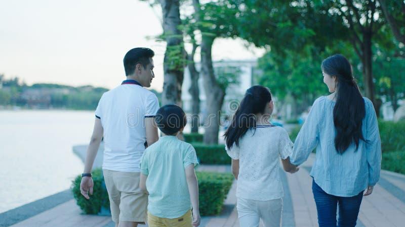 微笑&走在江边散步的亚洲家庭背面图在黄昏 库存照片