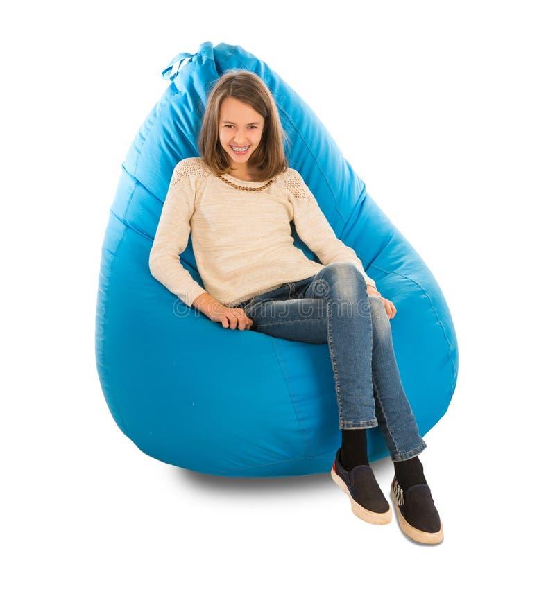 微笑年轻逗人喜爱的女孩,当坐蓝色装豆子小布袋时 免版税库存照片