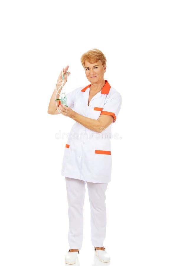 微笑年长女性医生或护士拿着氧气面罩 免版税库存图片